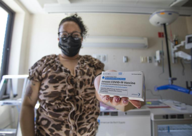 A woman holds a box containing COVID-19 vaccine.