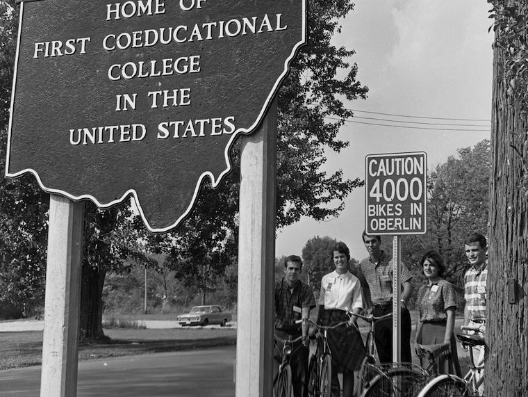 A small group of students stand next to a bicycle sign while holding their bikes.