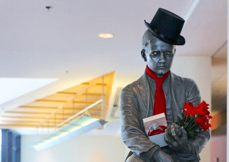 A statue of a man wearing a top hat and tie and carrying roses and a large diamond ring.