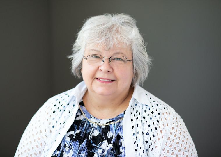 A portrait of an older woman wearing glasses.