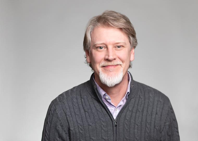 A portrait of a man wearing a sweater.