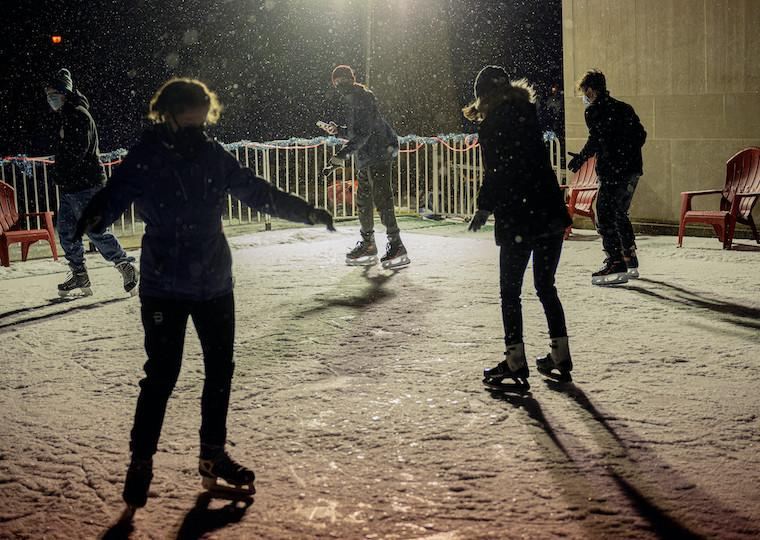 A group of people skate on an ice rink.