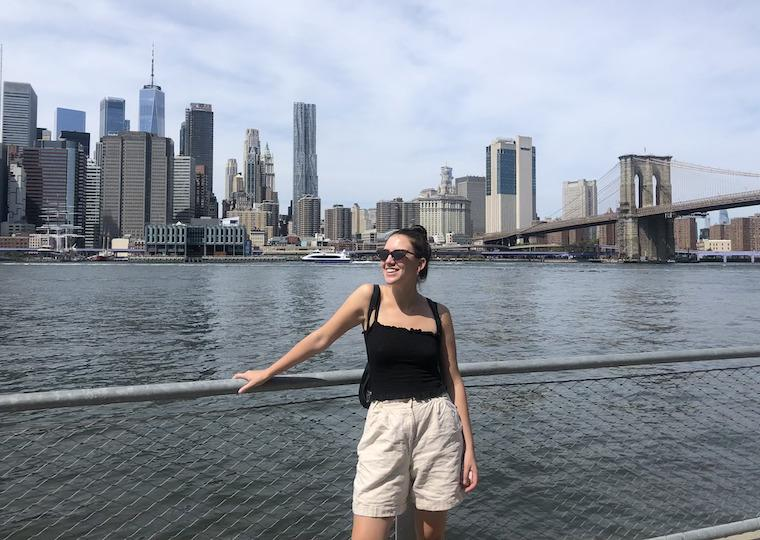 A woman stands next to a body of water across from downtown New York.