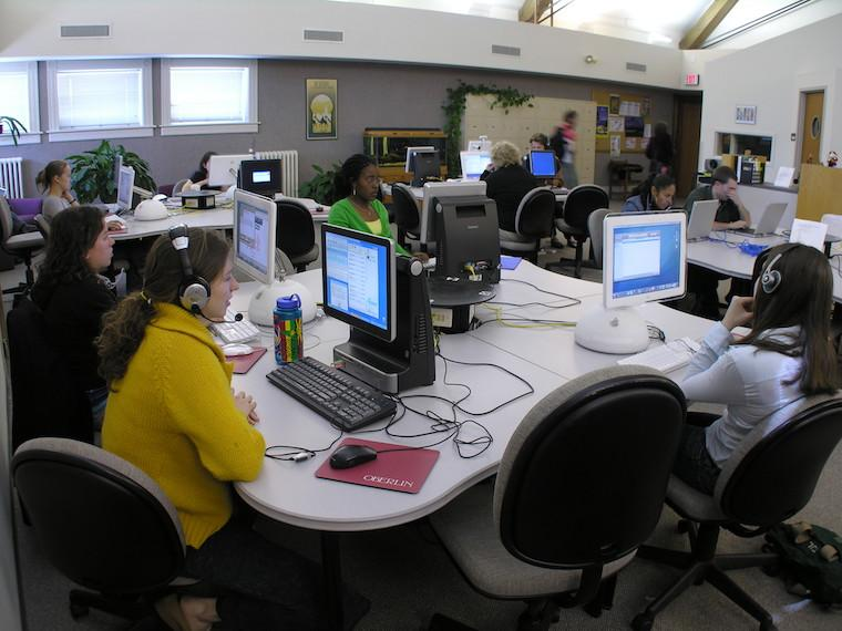 A computer lab with students wearing headphones and working on computers.