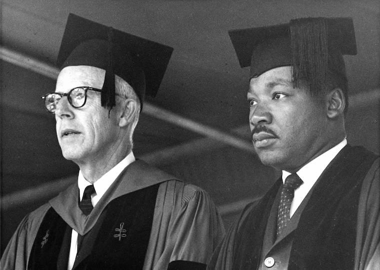 Two men wearing graduation caps and robes look out into a crowd.