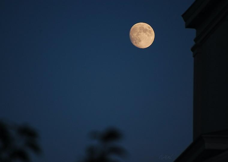 A full moon in a dark sky next to the silhouette of a building.