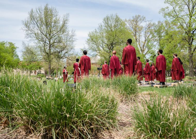 A group of people wearing choir robes stand in a field.