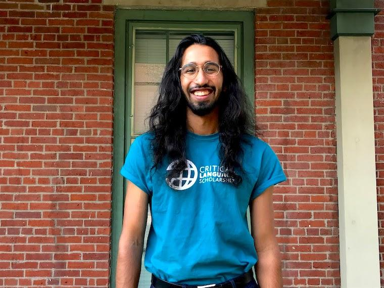 A portrait of a student with long hair and glasses.