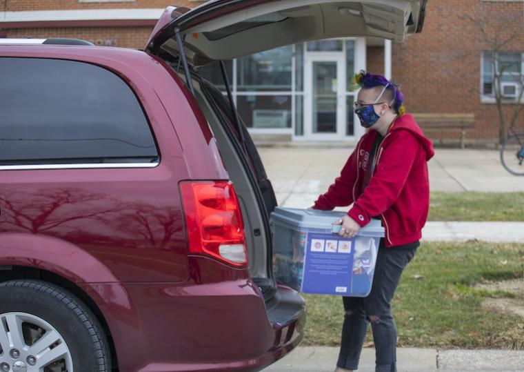 A student removes a large clear box from the trunk of a car.