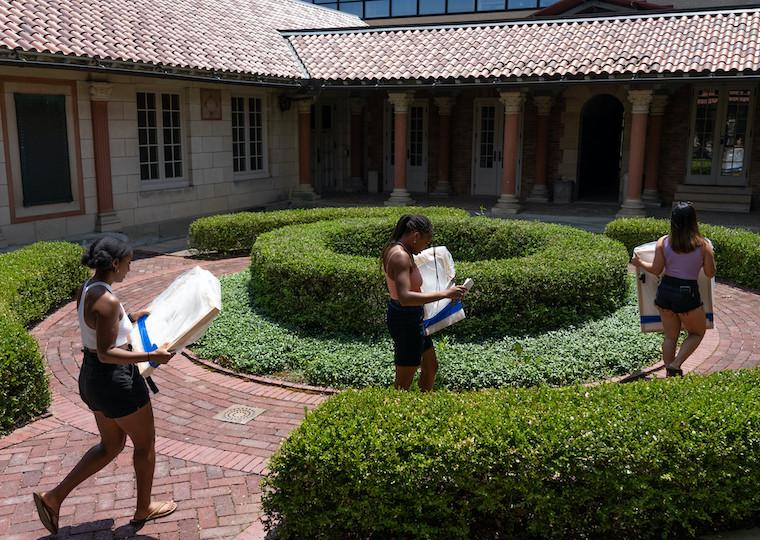Three students walk through a courtyard while holding pieces of artwork.