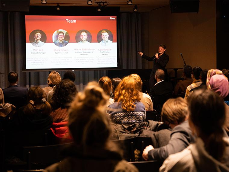 A large screen with the faces of the Twine app team, while an audiences watches.