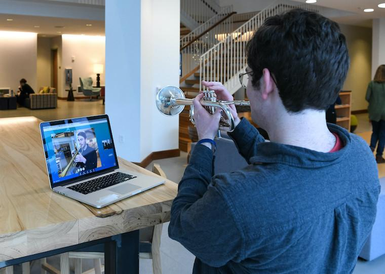A college student plays a trumpet while a person on a computer screen facing him plays a trumpet.
