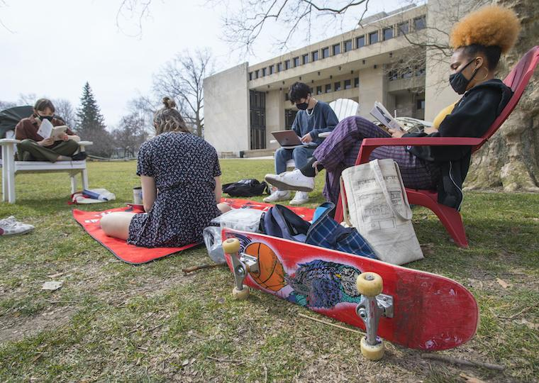 Students sit ion the lawn and in chairs as they study outside,