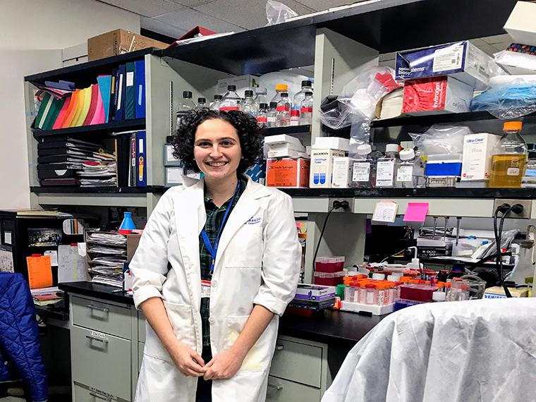 Lisa Learman, wearing a lab coat, stands in a science lab.