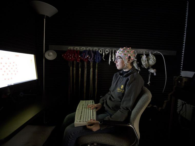 Student wearing white cap with wires coming from it sits in front of a computer screen in a dark room.