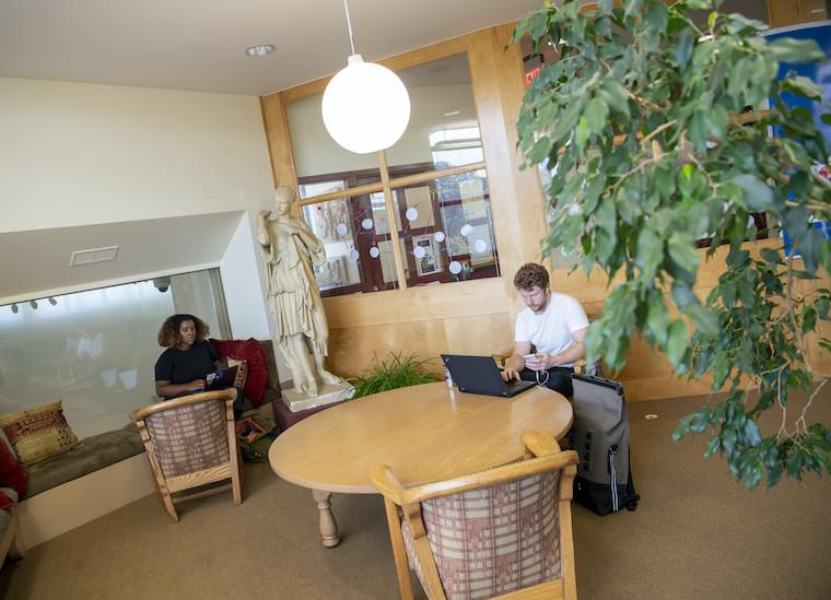 Two students study in a library nook.