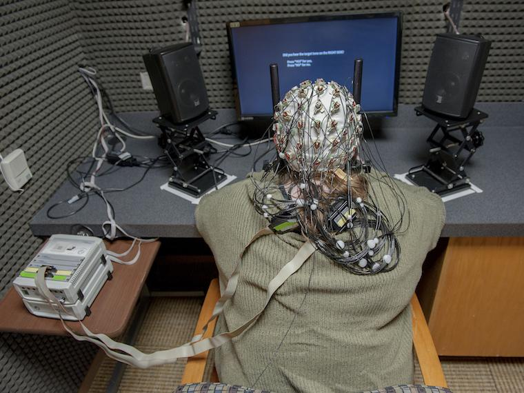 Student wearing a cap with wires coming from it sits in front of a computer screen.