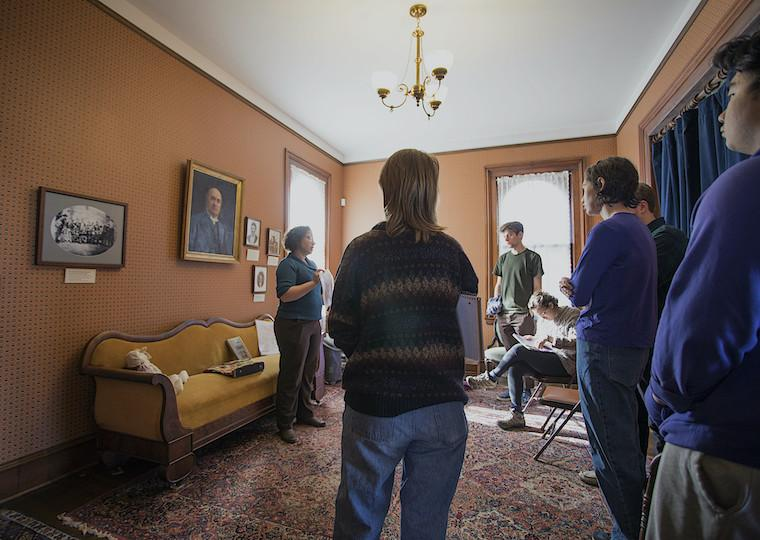 Students in a living room of a house turned into a museum.