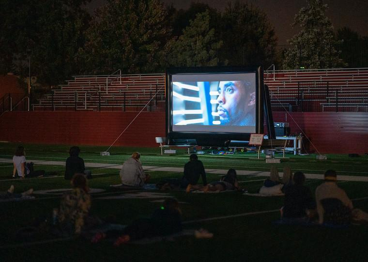 People watching a movie in a football field