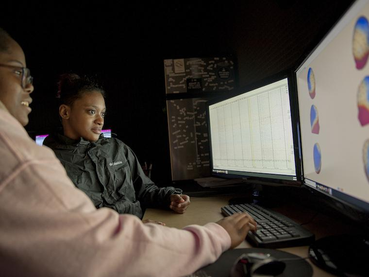 Two students look at images on a two large computer screens.