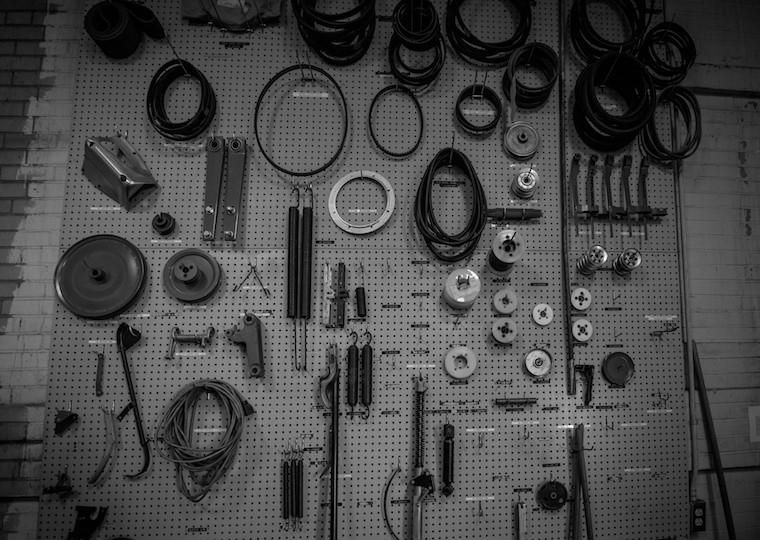 A pegboard filled with gears and belts.