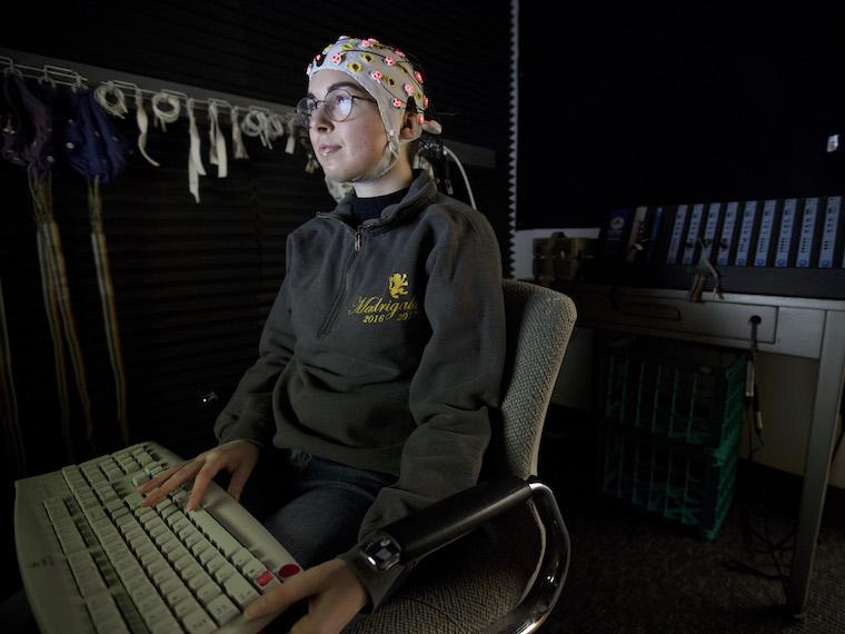 Student types on keyboard in a dark room, wearing a cap with suction cups.