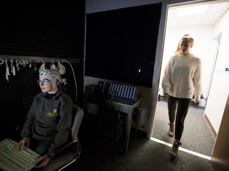 Student wearing white EEG hat sits in a dark room and another student walks in.