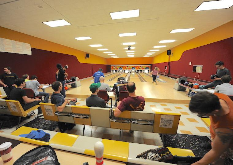 A bowling alley filled with people playing.