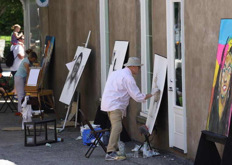 A row of artists draw on canvases in a small alley.