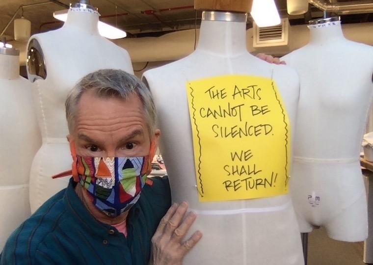 A man wearing a mask holds a mannequin wearing a sign.