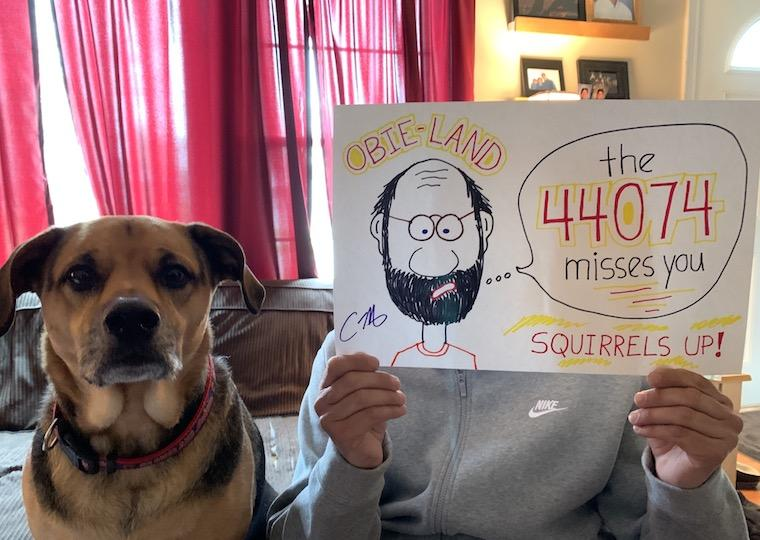 A man holds up a picture of himself with his dog sitting nearby
