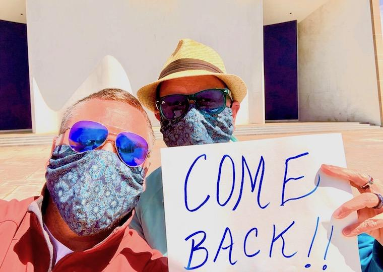Two men wearing masks and sunglasses hold a sign that says come back.