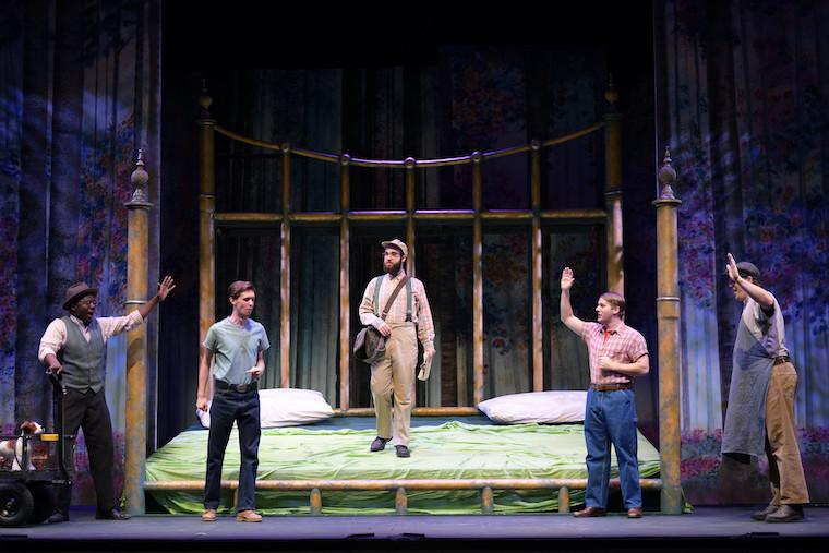 A large bed on a stage with five men standing on and near it.