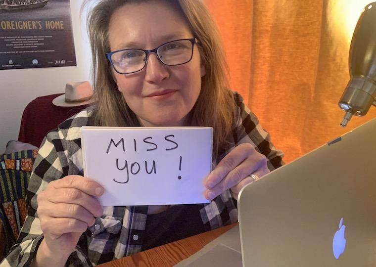 A woman holds a miss you sign.