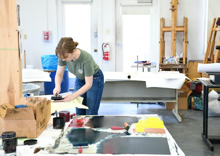 A student make wood print art in a studio.