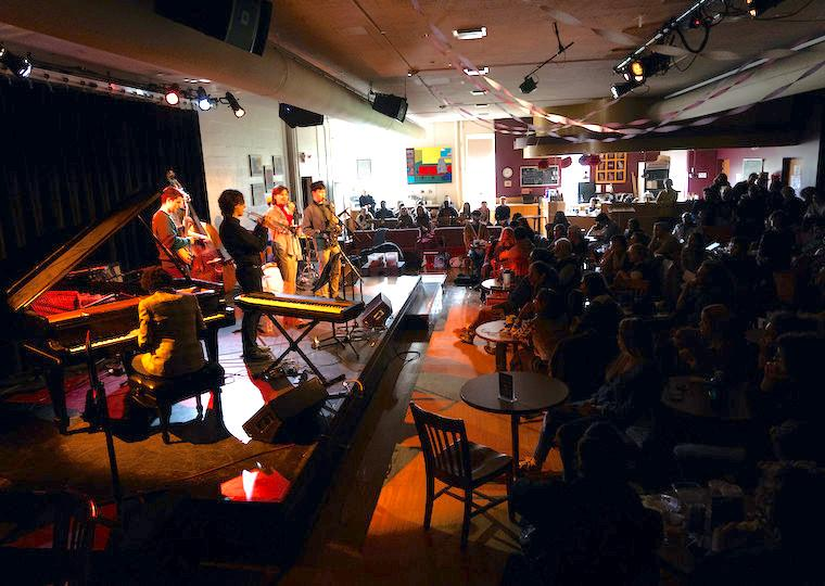 A large audience listens to a student jazz band on stage.