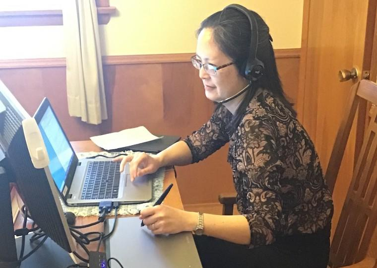 A woman wearing a headset, works on a laptop.