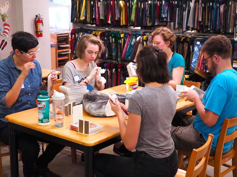 students at table cleaning CD and video cases