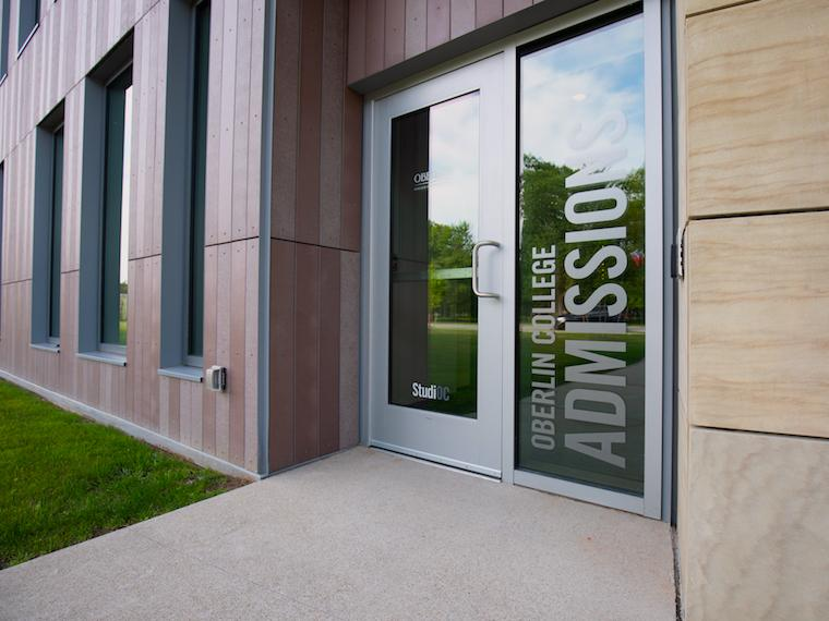 front entrance of admissions office with large glass door.