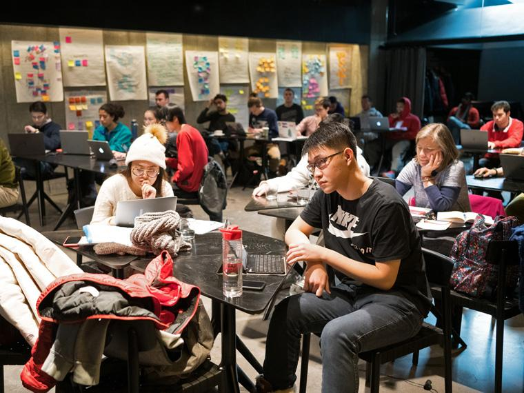 Groups of students work around small tables in the Birenbaum room.
