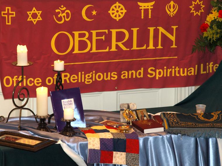 Oberlin banner behind a table set with religious artifacts, books