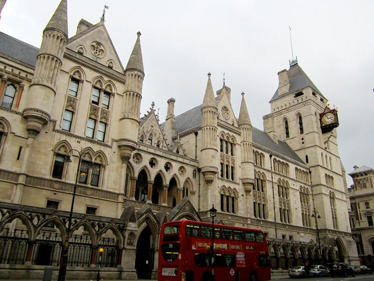 A double-decker bus pulls up in front of a large, gothic-style building.