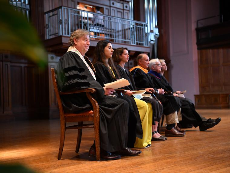 row of people dressed in graduate robes sitting on stage.