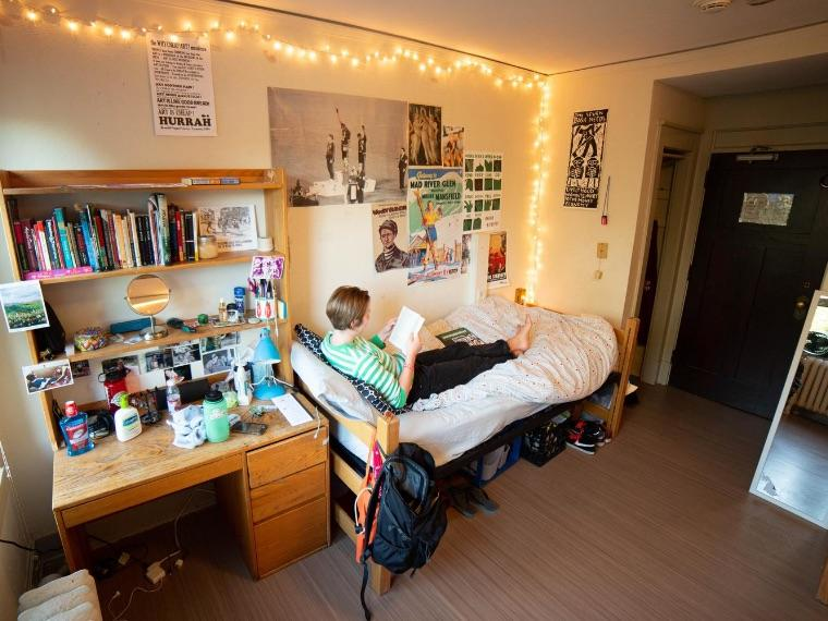 young woman sitting across a bed in dorm room