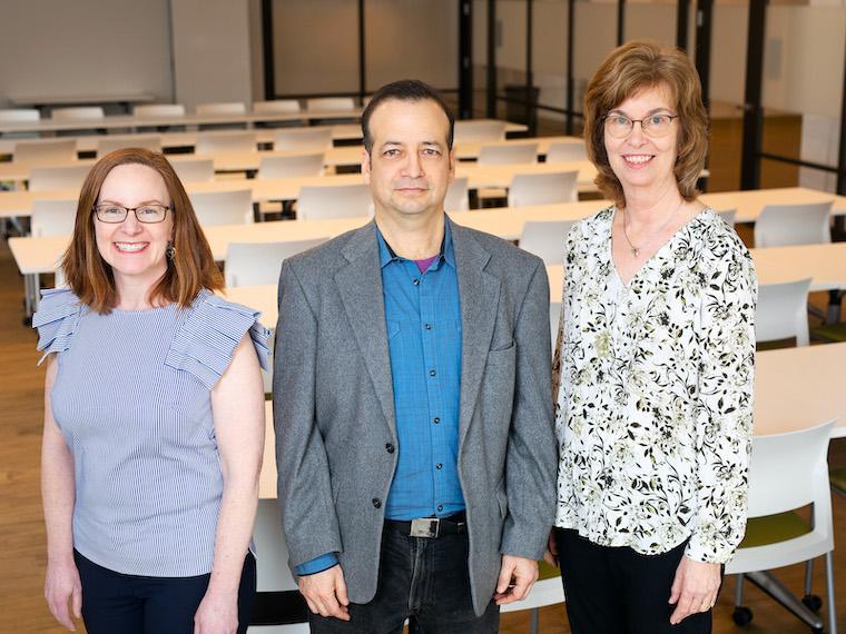 three people, woman, man, woman, standing in classroom