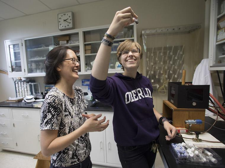 professor observing contents of a container a student is holding in her right arm
