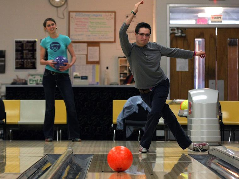 student tosses bowling ball down a lane as another student observes.