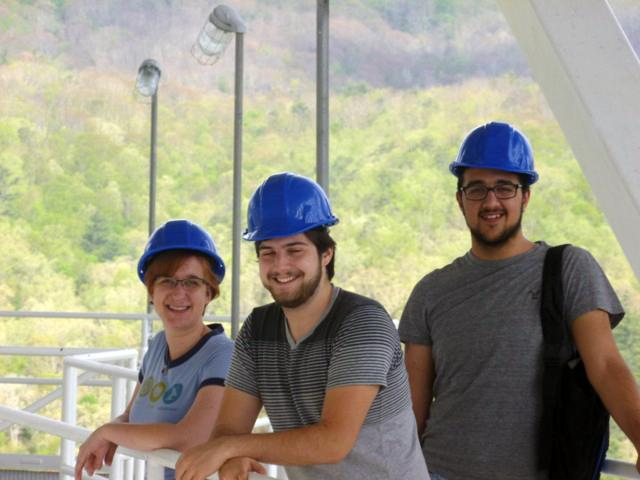 Three people in hard hats pose for a photo