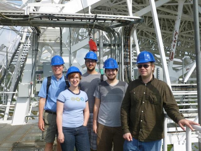 Five people in hard hats pose for a photo in front of a large structure