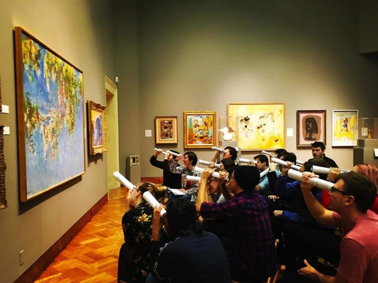 A group of people look at art, using rolled up paper as pretend telescopes